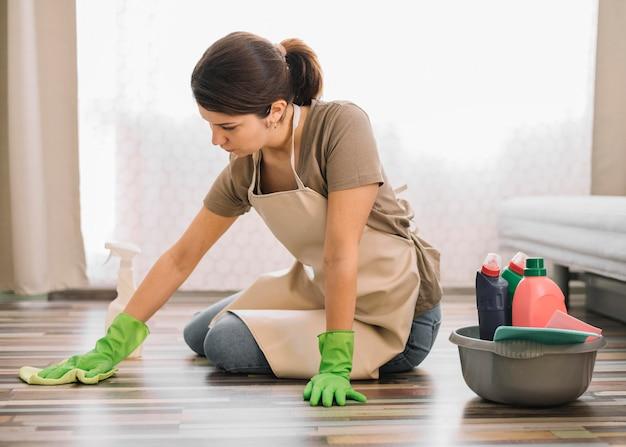 床を掃除して手袋を持つ女性