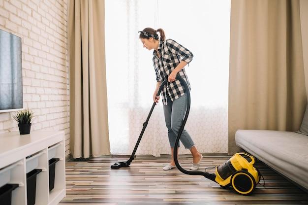 フルショットの女性がリビングルームで掃除機をかける