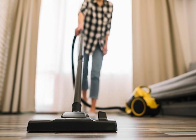 リビングルームで掃除機をかけるクローズアップの女性