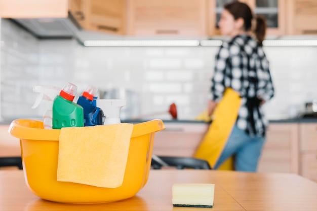 ぼやけている女性のクリーニングキッチン