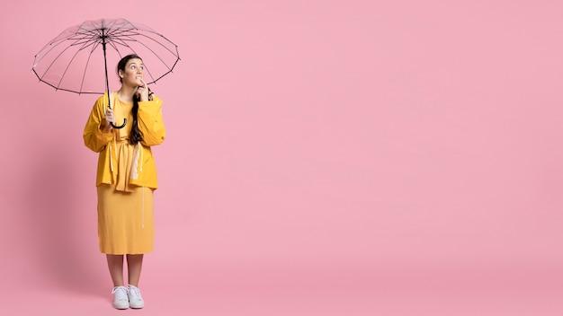 Женщина позирует, держа зонтик с копией пространства