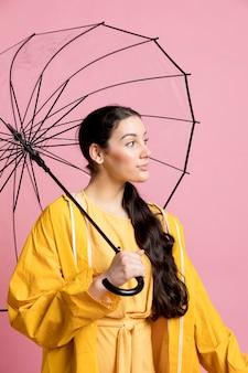 Женщина смотрит в сторону, держа зонтик