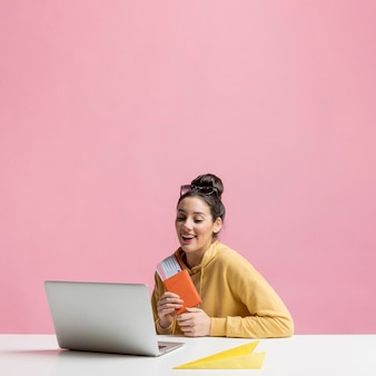 Счастливая женщина держит ее паспорт, глядя на свой ноутбук