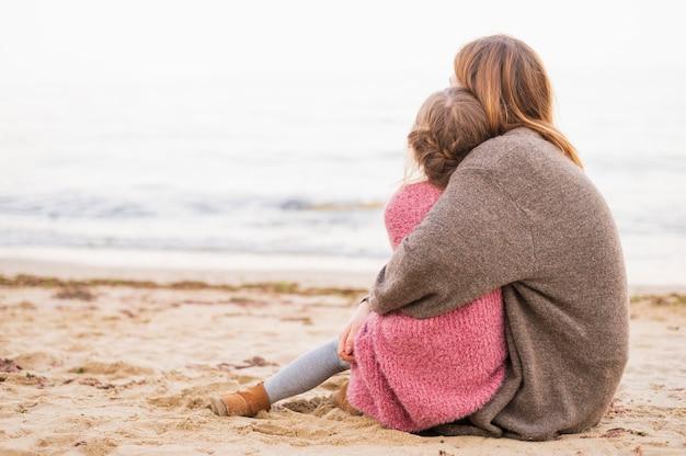 女性と子供の背面図を抱いて