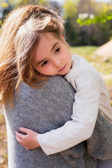 Маленькая девочка обнимает мать крупным планом