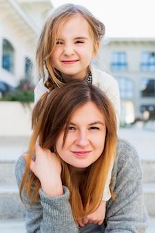 肩に女の子を運ぶ美しい母