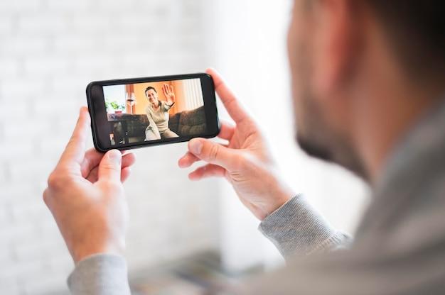 ビデオ通話を持つ男の正面図