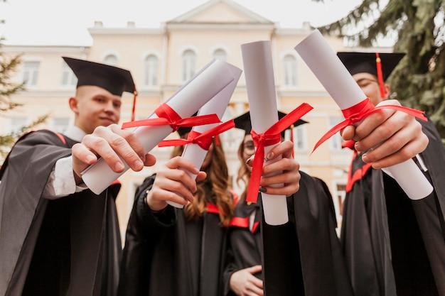 卒業証書を保持している若い学生
