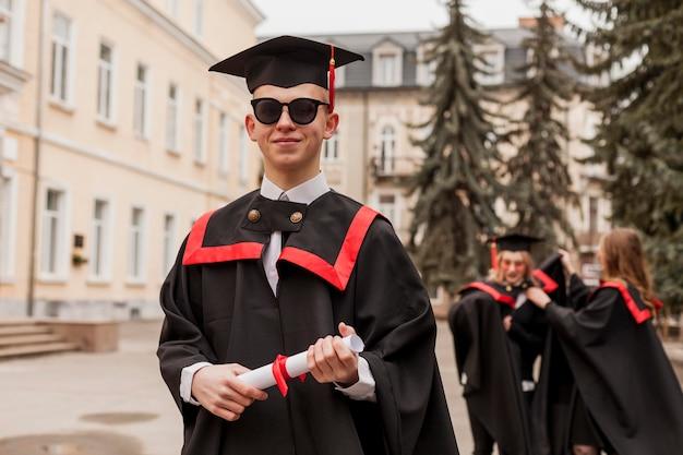 卒業証書を持つ正面学生