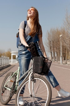 自転車に乗っている間、太陽を浴びて女性