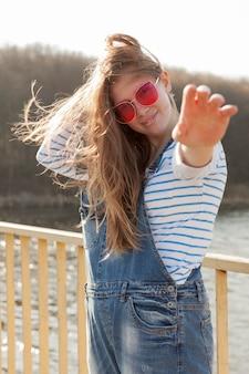 彼女の手を差し伸べている間ポーズのサングラスをかけた屈託のない女性の側面図