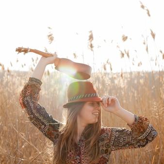 自由奔放な女性がウクレレで太陽の下でポーズ