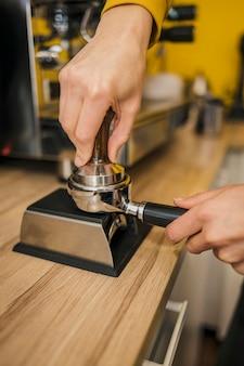 マシンのカップにコーヒーを詰めるバリスタの高角度