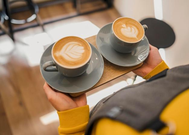 コーヒーのカップを提供するバリスタの高角度