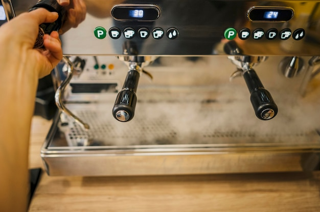 Высокий угол кофемашины с баристой, управляющей им