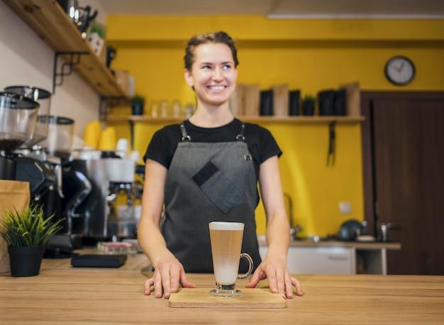 コーヒー飲料と女性のバリスタの正面図