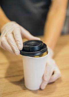 ラテックスグローブ付きのコーヒーカップを扱うバリスタの高角度