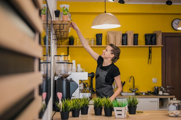 コーヒーショップで働く女性のバリスタの側面図