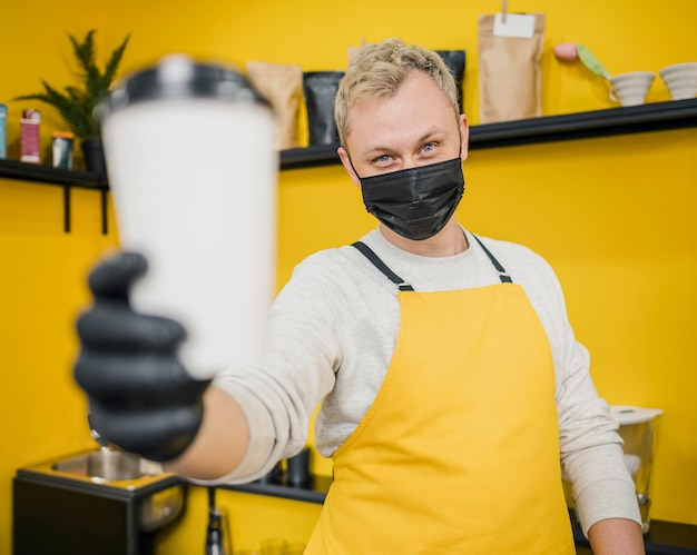 コーヒーカップを保持している医療マスクを持つ男性のバリスタ