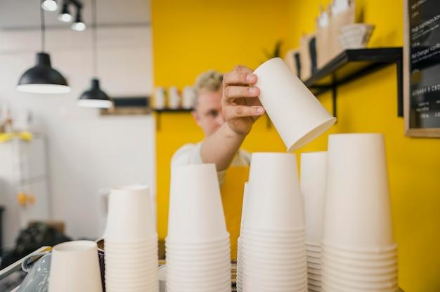 Вид спереди мужской бариста с кофейными чашками