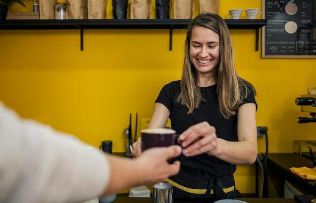 一杯のコーヒーを渡すスマイリー女性バリスタの正面図