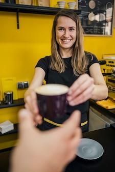 一杯のコーヒーを渡す女性バリスタの正面図