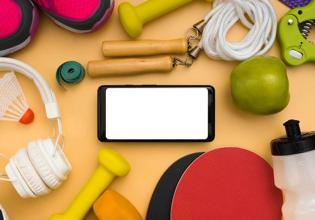 スポーツの必需品とヘッドフォンを備えたスマートフォンのフラットレイアウト