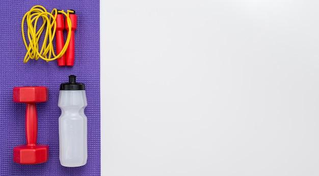 Вид сверху скакалка с бутылкой с водой и весом