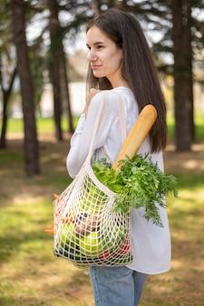 外の再利用可能なバッグを保持している女性