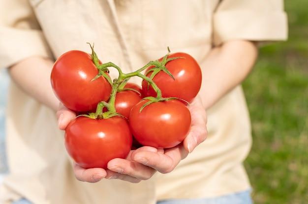 外のトマトを保持しているクローズアップの女性