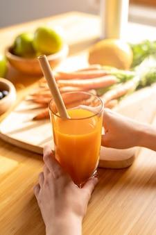 Высокий угол женщина руки, держа бокал с морковным соком