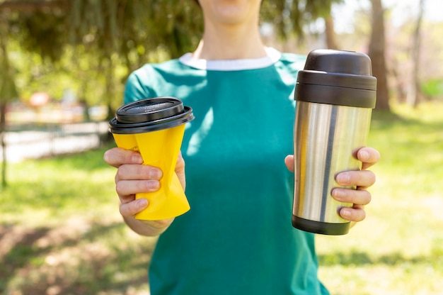 魔法瓶とプラスチックカップを保持しているクローズアップの女性