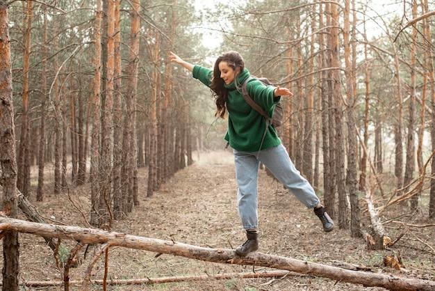 倒れた木の上を歩く女性