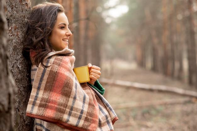 毛布と紅茶のカップを持つ女性