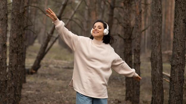 ヘッドフォンで自然の中で女性