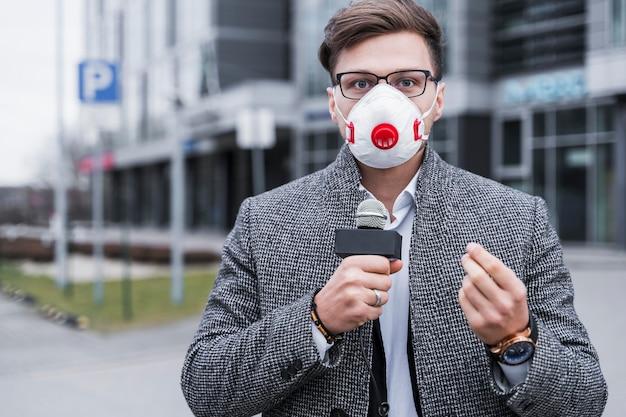 マスクを持つジャーナリストの男
