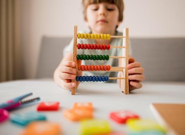 Вид спереди ребенка с помощью счеты в домашних условиях