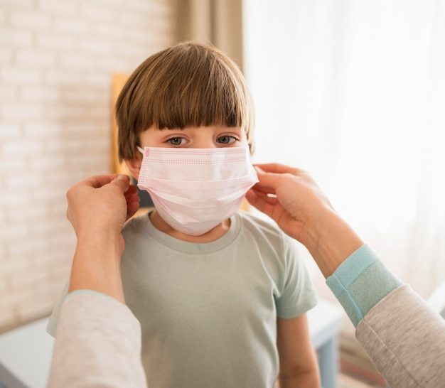 Женщина надевает на ребенка медицинскую маску