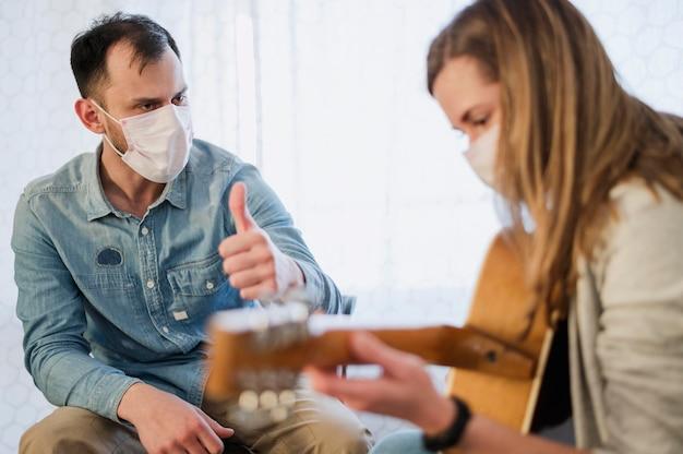 Учитель гитары дает большие пальцы руки студентке