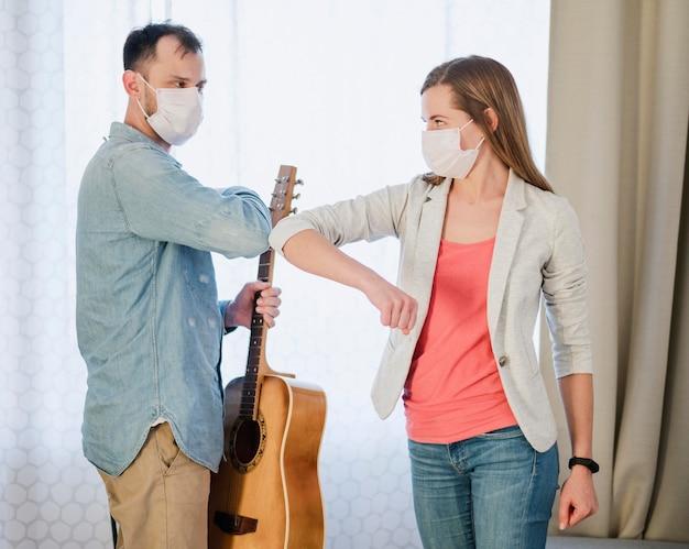 Вид сбоку локтя женщины, приветствуя ее учитель гитары