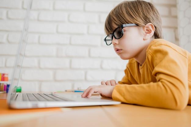 Вид сбоку ребенка в очках, глядя на ноутбук