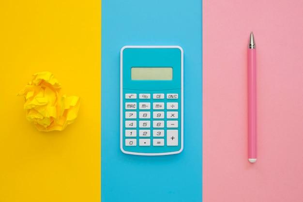 Плоский лежал калькулятор с ручкой и мятой бумагой