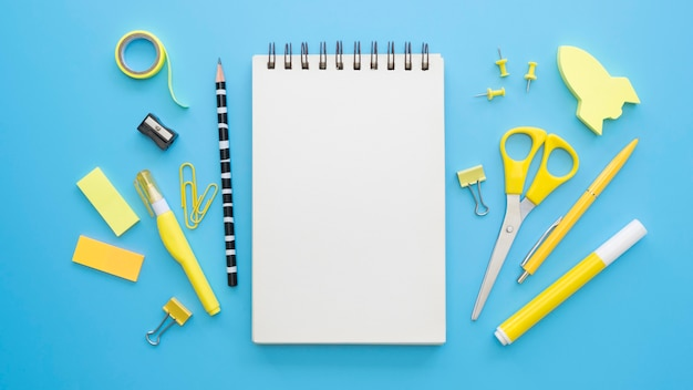 ノートブックとはさみとオフィス文具のフラットレイアウト