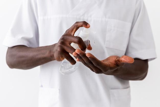 専門の男性医師が手の消毒剤を使用