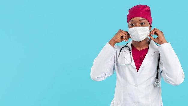 女医が彼女の外科医のマスクを調整します