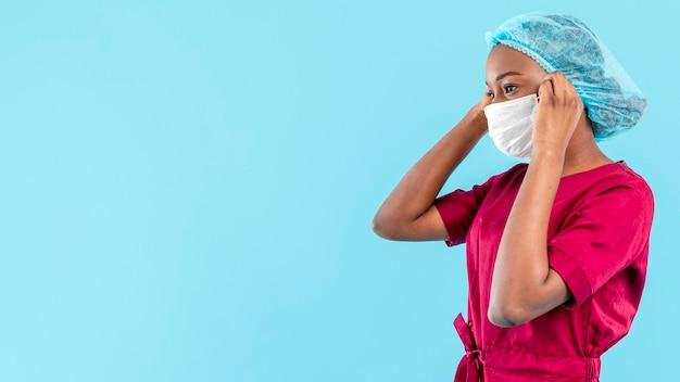 女医が彼女の医療マスクを配置