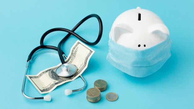 医療マスクとしわくちゃのお金を身に着けている貯金箱