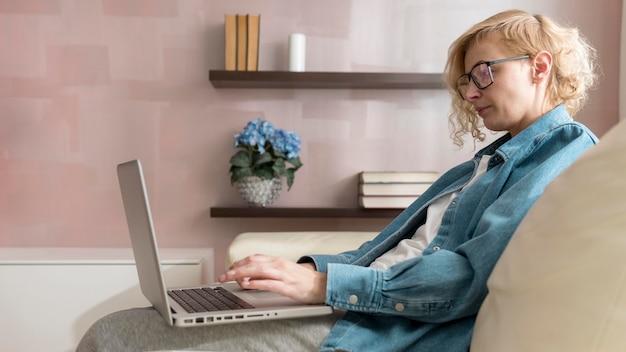 Середине выстрел женщина сидит на диване и работает на ноутбуке