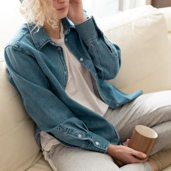 Женщина высокого угла слушая к музыке и держа кружку кофе