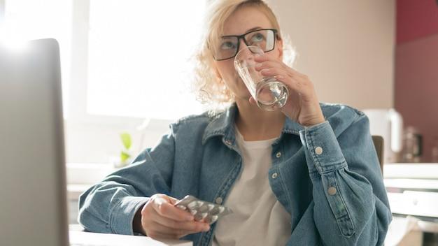 ノートパソコンの近くの薬を飲んでいるブロンドの女性